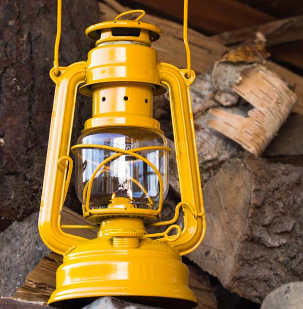 Bilden visar en gul lykta från Feuerhand. I bakgrunden syns vedträn.