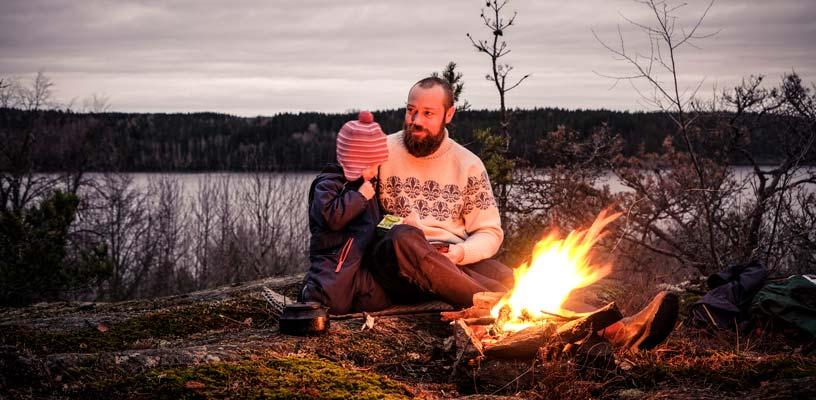 Ett barn och en vuxen har tänt en brasa uppe på ett berg intill en sjö. De sitter intill elden och värmer sig i höstkylan och kaffe kokas i en kanna.