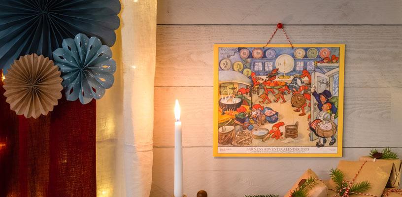 Levande ljus brinner och skapar en härlig stämning. Barnens adventskalender hänger på väggen och julklappar skymtas på bordet