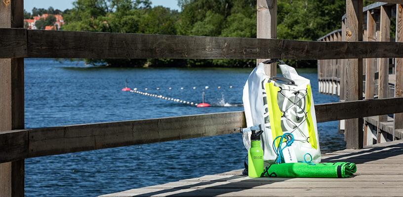 Ryggsäck, handduk, powerbank ligger på en brygga med vattnet i bakgrunden. Solen skiner och himlen är klarblå.