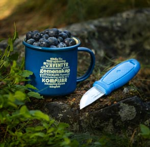 En blå emaljmugg med Scouternas värdeord tryckt i beige står i blåbärsris tillsammans med en kniven Eldris från Morakniv. Muggen är fylld till kanten med nyplockade blåbär.