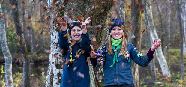 Två glada scouter kastar upp höstlöv i luften