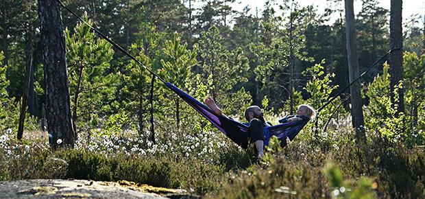 Två personer sitter i en hängmatta ute i den grönskande naturen.
