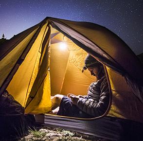 Natthimlen är stjärnklar, en person sitter i ett tält som är upplyst.